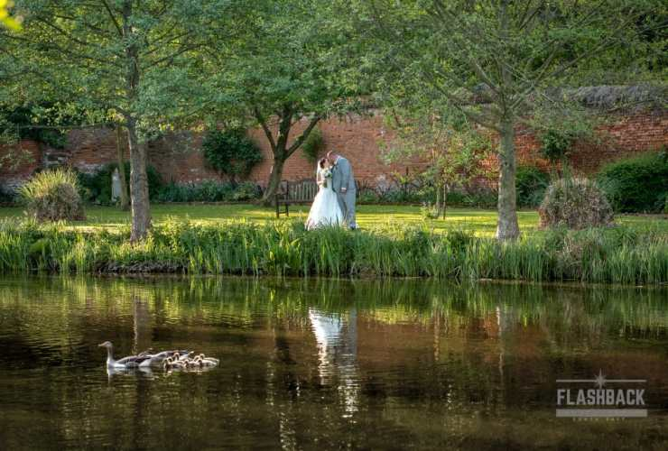 Bride and Groom kissing behind a lake. Kent Sussex Surrey Essex