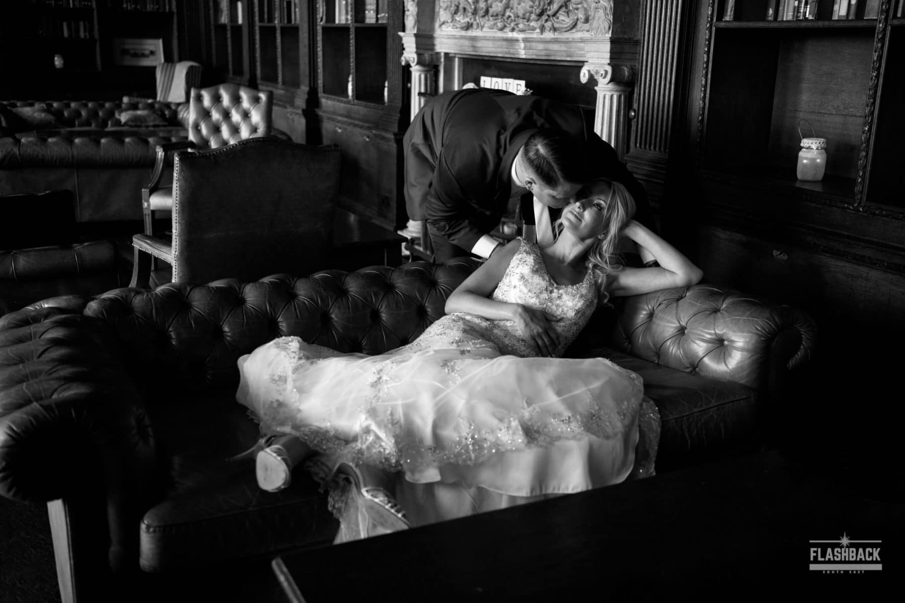 Bride sitting on a sofa with Groom leaning in for a kiss. Relaxed wedding photography