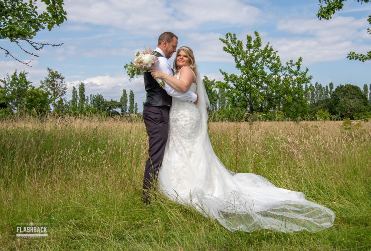 Bride and Groom standing in the Knowle's grounds hugging.