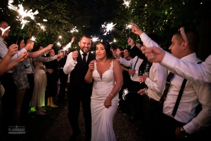 Bride and Groom walking through archway of sparklers in Essex Page:Wedding planning is a lot of work and expensive!