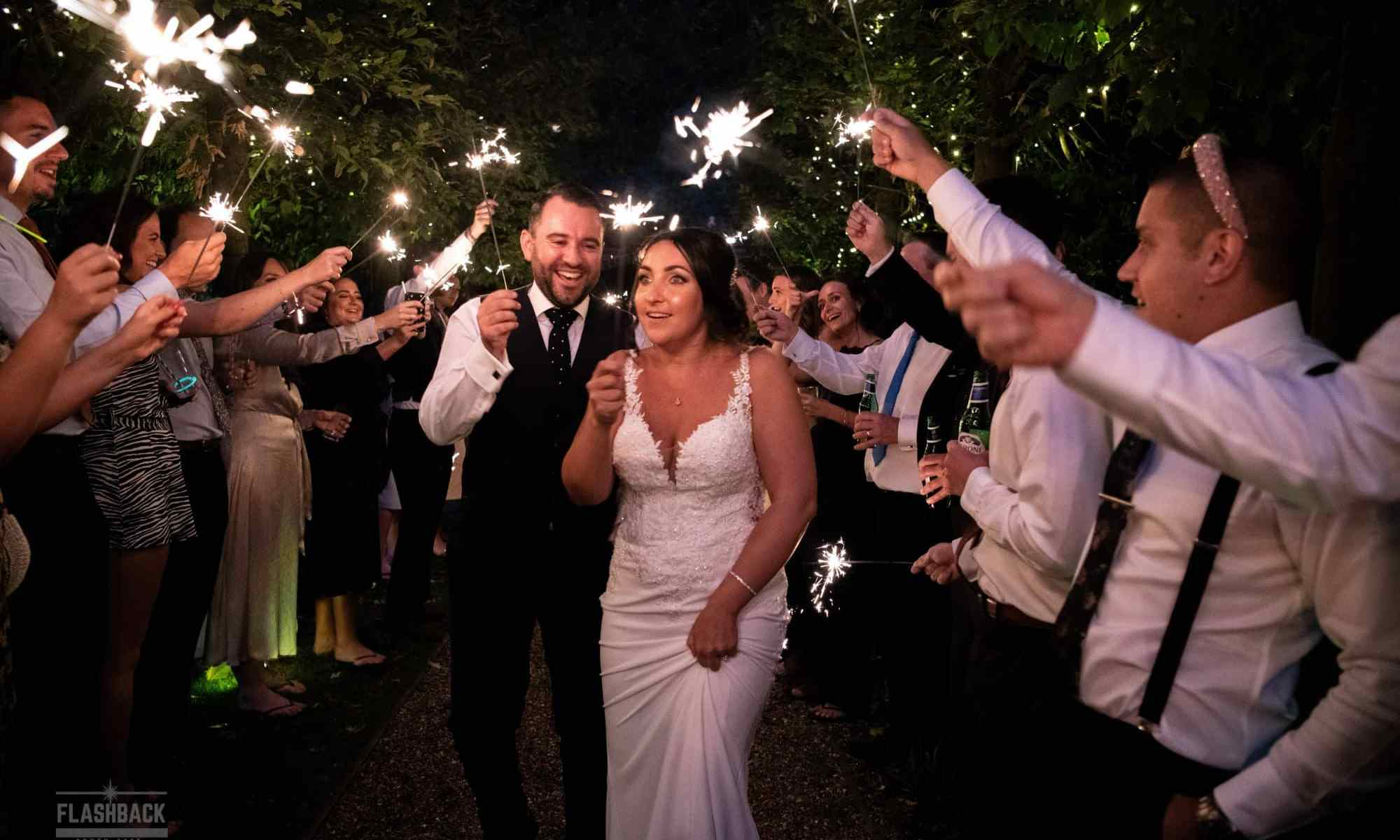 Essex Wedding Photography Bride and Groom walking through archway of sparklers in Essex Page:Wedding planning is a lot of work and expensive!
