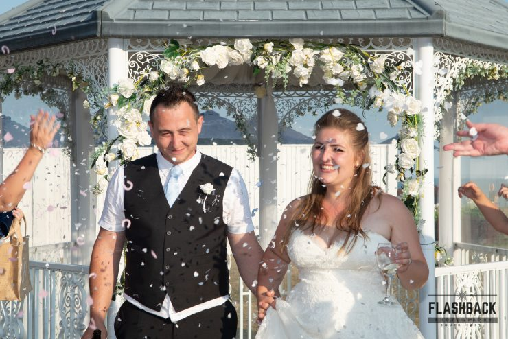 Bride and Groom under archway with confetti. Kent Sussex Surrey Essex