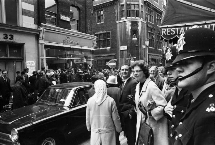 11 мая 1966 года. Полиция прибыла на Карнаби-стрит в Лондоне, чтобы допросить владельца бутика Генри Мосса и модели Дайан Джеймс и Джину Бейкер после того, как они вызвали заторы на улице, переодевшись в витрине магазина.  (Фото МакКауна / Экспресс / Getty Images)