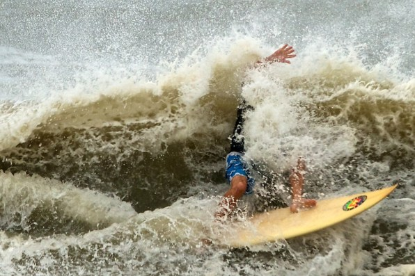 A surfer hits the break of an eight foot wave at Folly Beach in Charleston, S.C., Friday, Aug. 26, 2011, as Hurricane Irene causes larger than normal swells along the South Carolina coast. (AP Photo/Brett Flashnick)