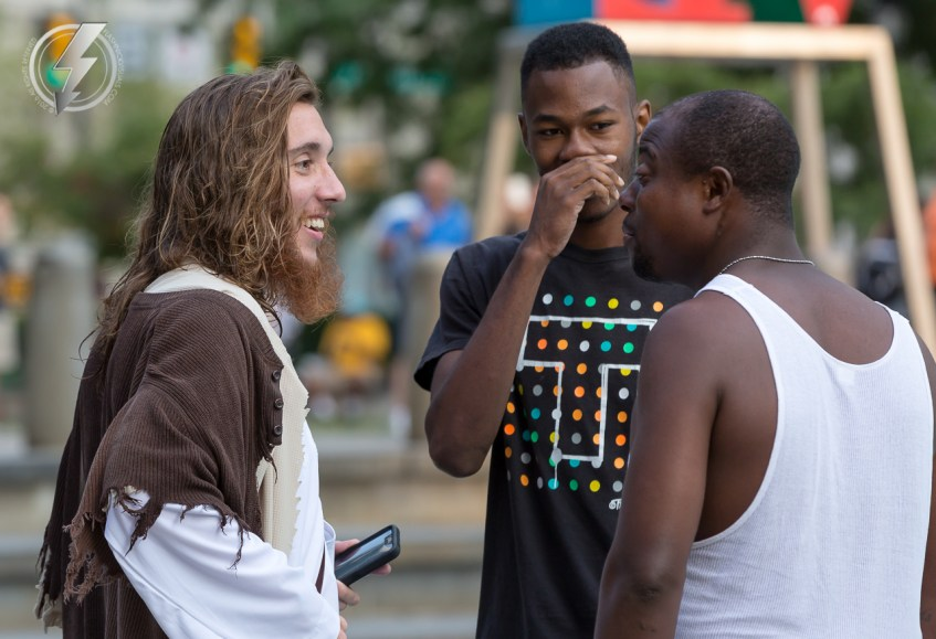 """Michael Grant, also known as """"Philly Jesus"""" talks to two men about his faith at JFK Plaza in Philadelphia, PA on Wednesday, July 30, 2014. For the last three months, Grant has dressed as Jesus Christ, and walked the streets of Philadelphia to share the Christian gospel by example."""