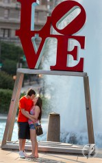 A young couple kisses while posing for a portrait in front of the famous LOVE sculpture by Robert Indiana at JFK Plaza (aka Love Park) in Philadelphia, PA.