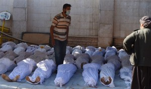 """Syrian activists inspect the bodies of people they say were killed by nerve gas in the Ghouta region near Damascus on Wednesday."" (source: Reuters)"