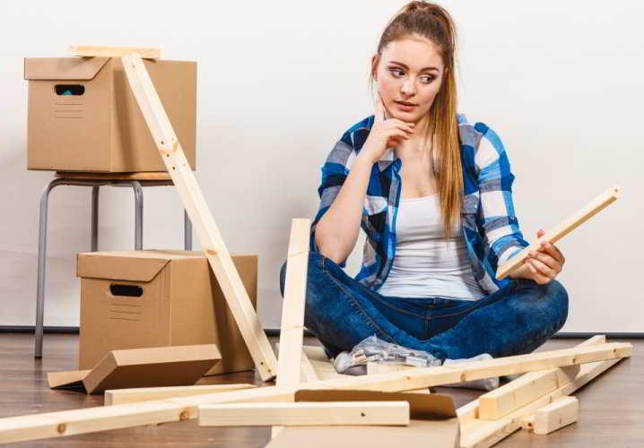 Girl Struggling with Flatpack Furniture Assembly
