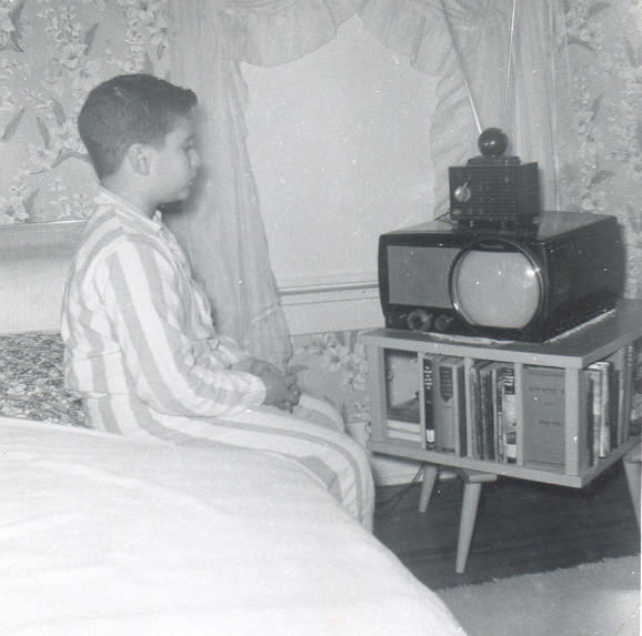 1955 photo of Harry Friedman as a boy, watching TV while sitting on the edge of a bed