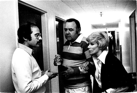 Harry Friedman, left, talks in a hallway with comedians Jonathan Winters and Joan Rivers.