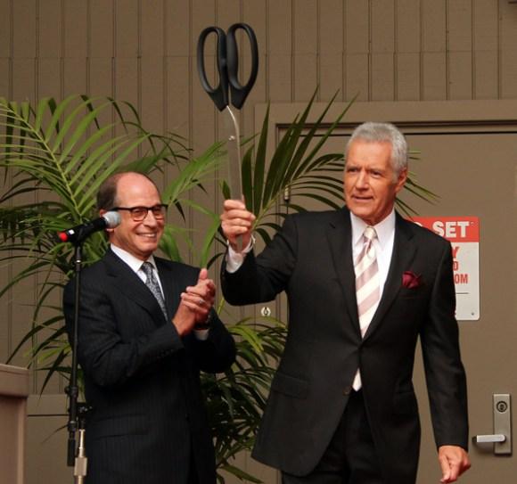 Harry Friedman, left, claps while Alex Trebek holds a giant pair of scissors.