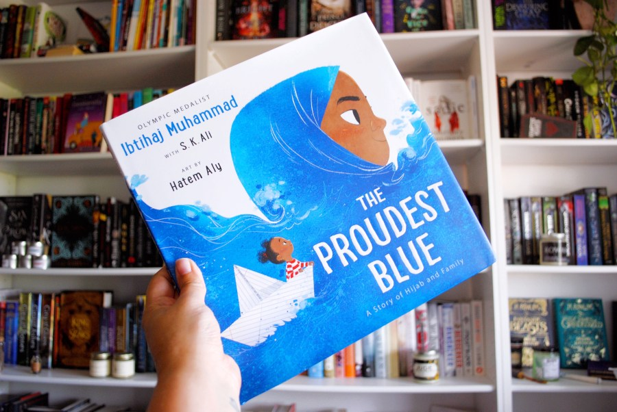 Photograph of me holding a copy of The Proudest Blue