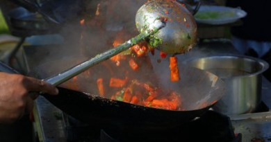 Image of vegetables being tossed in a sizzling wok