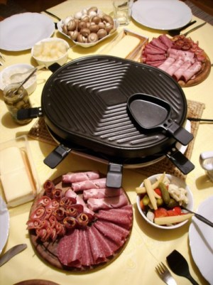 Image of a tabletop raclette grill, surrounded by dishes of deli meats, and pickled vegetables