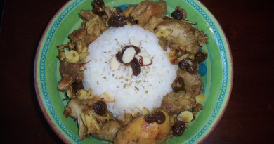 Top view of a blue and green bowl filled with a mound of white rice ringed with pieces of cooked chicken, sliced almonds, raisins, and chopped garlic.