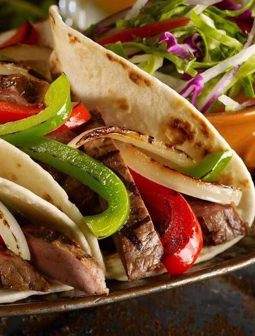 Classic Tex Mex, fajitas are typically made with grilled flank steak with onions and bell peppers, and served sizzling hot with fresh tortillas, guacamole, sour cream, and salsa.