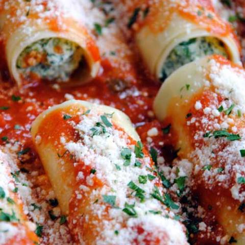 Recipe for Ricotta and Spinach Manicotti - These manicotti are filled with a blend of ricotta, mozzarella and fresh spinach then topped with a tomato basil sauce and Parmigiano-Reggiano for a cheesy, flavorful dish that will wow your dinner guests.