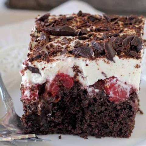 This Black Forest Poke Cake is a gooey chocolate cake filled with hot fudge and cherry pie filling. It's topped with fresh whipped cream and chocolate shavings.