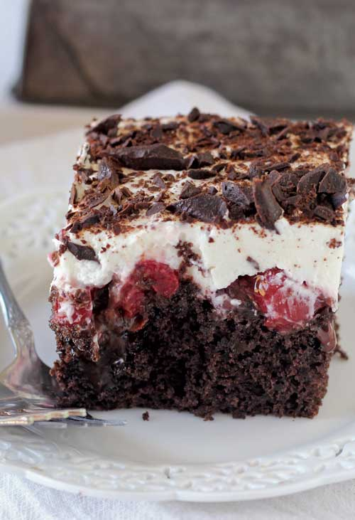 This Black Forest Poke Cake is a gooey chocolate cake filled with hot fudge and cherry pie filling. It is topped with fresh whipped cream and chocolate shavings. #chocolate #cake #dessert #cherries #pokecake