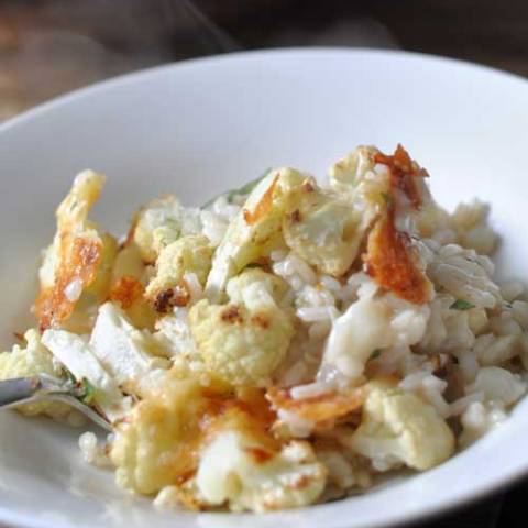 Recipe for Roasted Cheesy Cauliflower Risotto - Texture and flavor all rolled into one bubbling pan of arborio. Caramelised, cheesy bits in the roasted parts, and the soft, flavor-soaked bits care of the risotto.