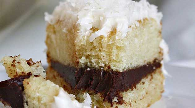 Recipe for Coconut Layer Cake with Chocolate Ganache Filling - If you like chocolate and coconut together, you're going love this cake topped with Swiss meringue buttercream and coconut flakes!