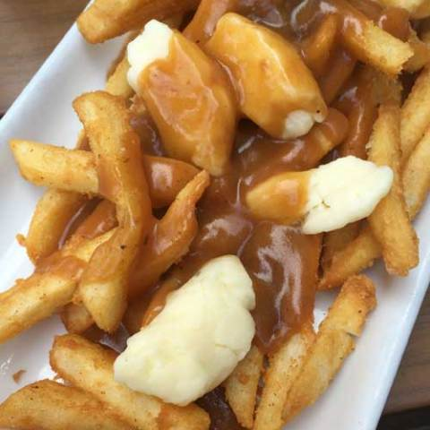 Recipe for Traditional Canadian Poutine - French Fries with Gravy and Cheese Curds - A savory mound of french-fried potatoes topped with beef gravy and fresh cheese curds. Poutine is one the ultimate late-night snacks.