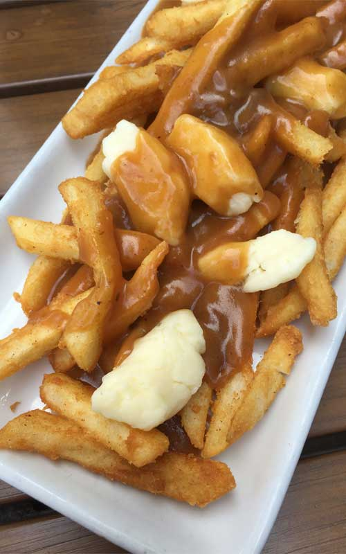French Fries with Gravy and Cheese Curds - A savory mound of french-fried potatoes topped with beef gravy and fresh cheese curds. This Traditional Canadian Poutine is one the ultimate late-night snacks.