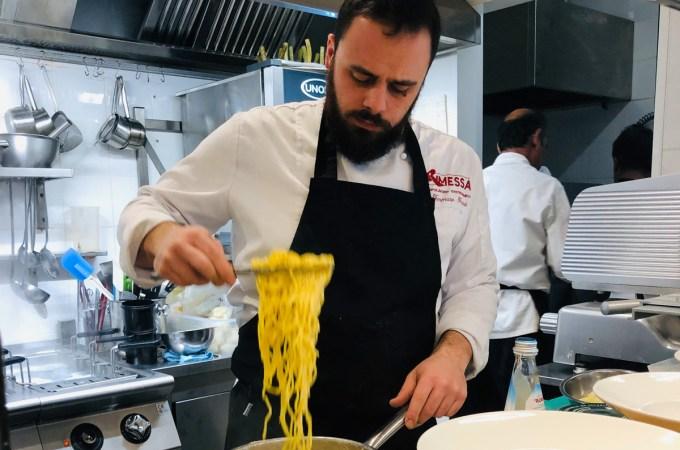 Chef plating a delicious pasta dish at Rimessa Roscioli in Rome
