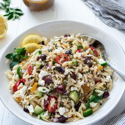 greek orzo pasta salad in a white bowl with spoon buried into the side