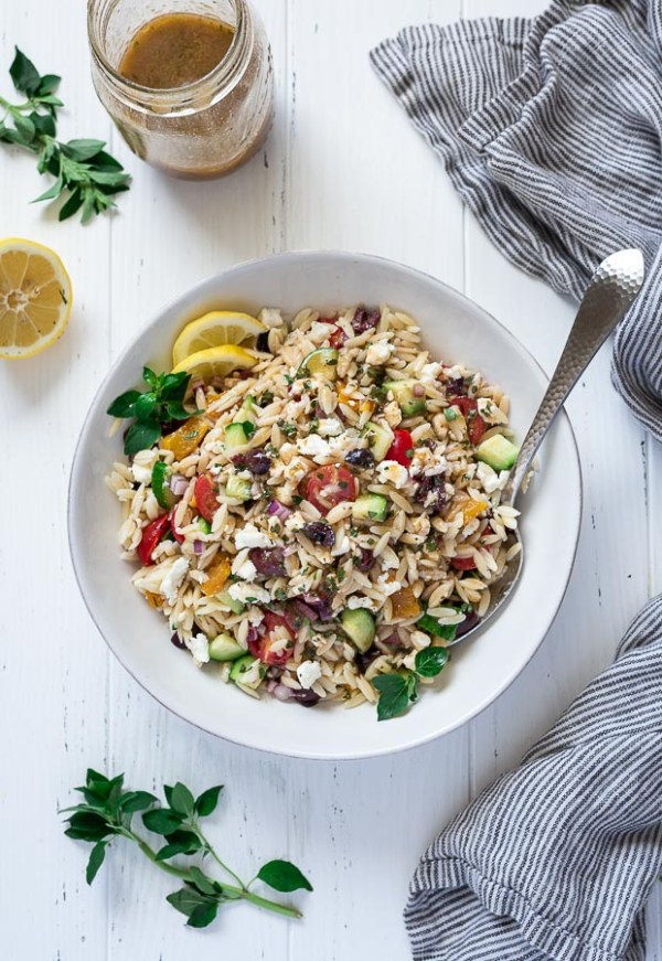 overhead shot of greek orzo salad in a bowl with a spoon, lemon slices and oregano