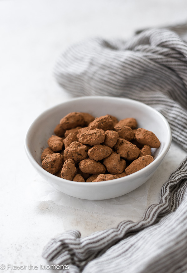 front view of almond dragees in a white bowl with a linen