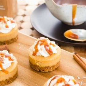 mini pumpkin cheesecakes on wooden cutting board with cinnamon stick