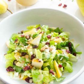 Cranberry Pear Salad with Fresh Pear Vinaigrette is an addicting blend of crisp romaine, juicy pear, dried cranberries, feta cheese, and toasted almonds tossed ina fresh pear vinaigrette!