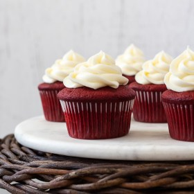 front shot of red velvet cupcakes on wicker pedestal