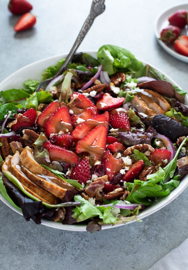 close up of strawberry fields salad with balsamic dressing on top and spoon buried inside bowl