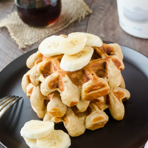 banana greek yogurt waffles stacked on a plate with sliced bananas