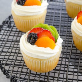 Fruit Tart Vanilla Cupcakes are light vanilla cupcakes filled with pastry cream and topped with fresh fruit and whipped cream. They're like a fresh fruit tart in cupcake form! @FlavortheMoment