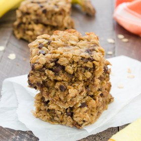 Peanut Butter Banana Chocolate Chip Oat Bars stacked up on parchment paper