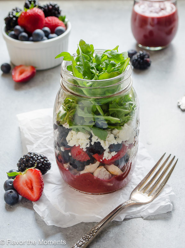 Mixed Berry Balsamic Mason Jar Salad is packed with chicken, mixed berries, feta, and arugula with a mixed berry balsamic vinaigrette. It's the perfect summer salad for people on the go! @FlavortheMoment