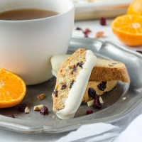 cranberry orange biscotti on a silver plate with tea and orange