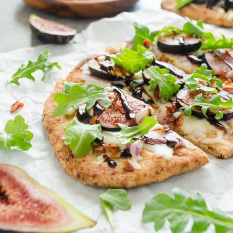 fig pizza sliced with fresh arugula on top