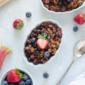 slow cooker fruit crisp in white ramekin with berries on top