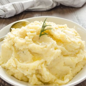 slow cooker mashed potatoes in white serving bowl