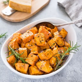 front view of roasted sweet potatoes in white serving bowl with spoon