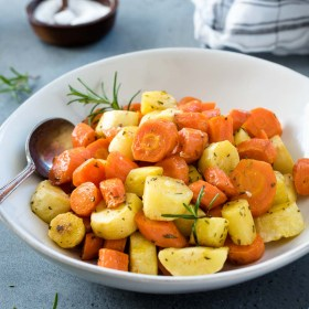 roasted carrots and parsnips in a white bowl with serving spoon