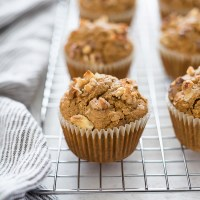 Flourless carrot cake oatmeal muffins on a wire rack with linen