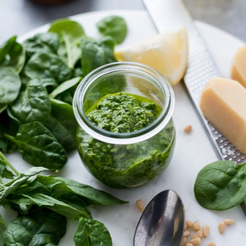 Pesto sauce in jar with spinach, parmesan cheese and lemon
