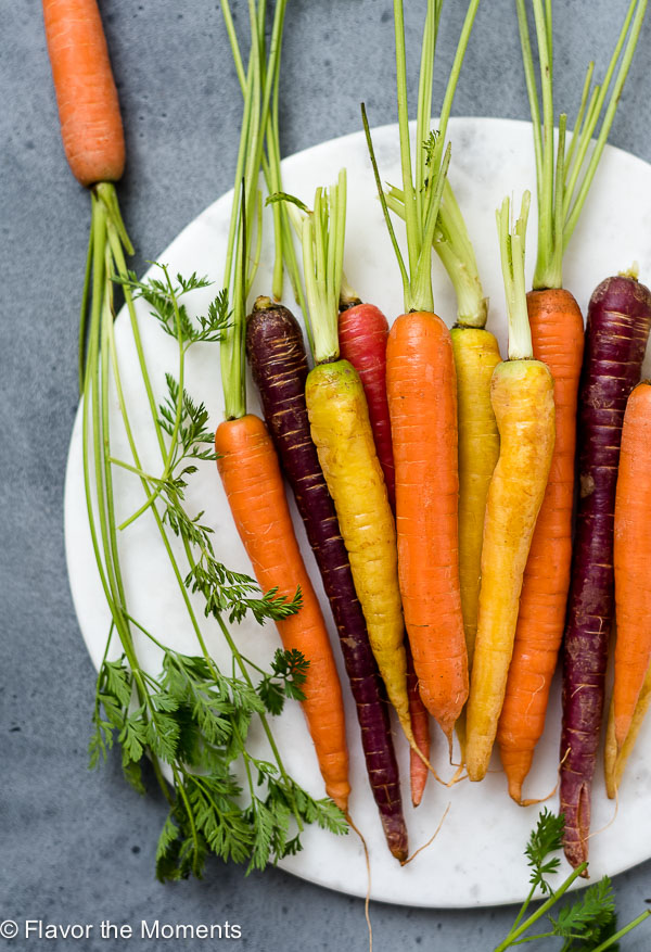 close up overhead shot of carrots and carrot tops on a white marble board for carrot produce guide