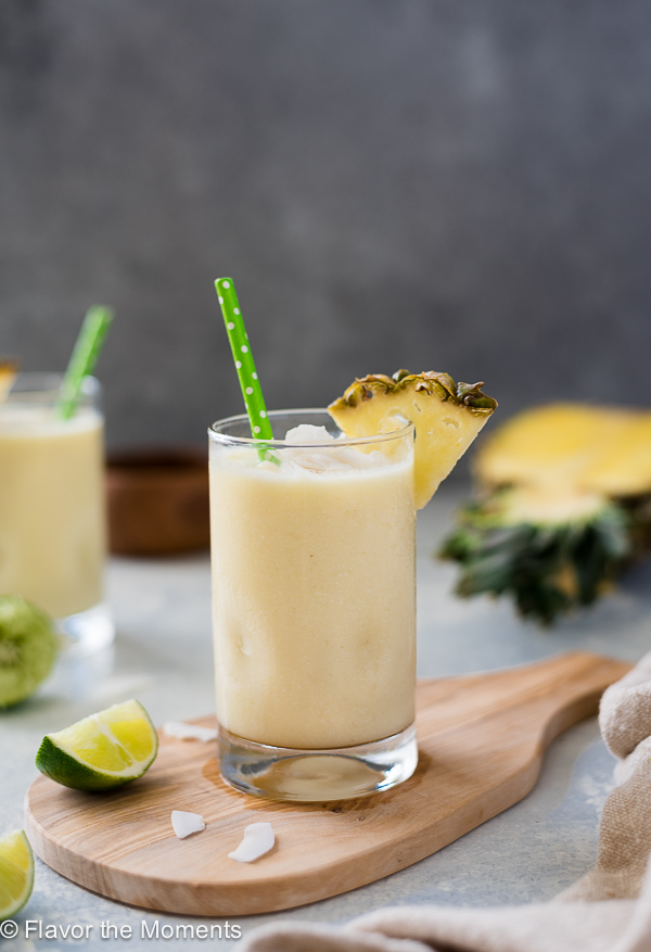 front view of pina colada smoothie with green straw and pineapple slice