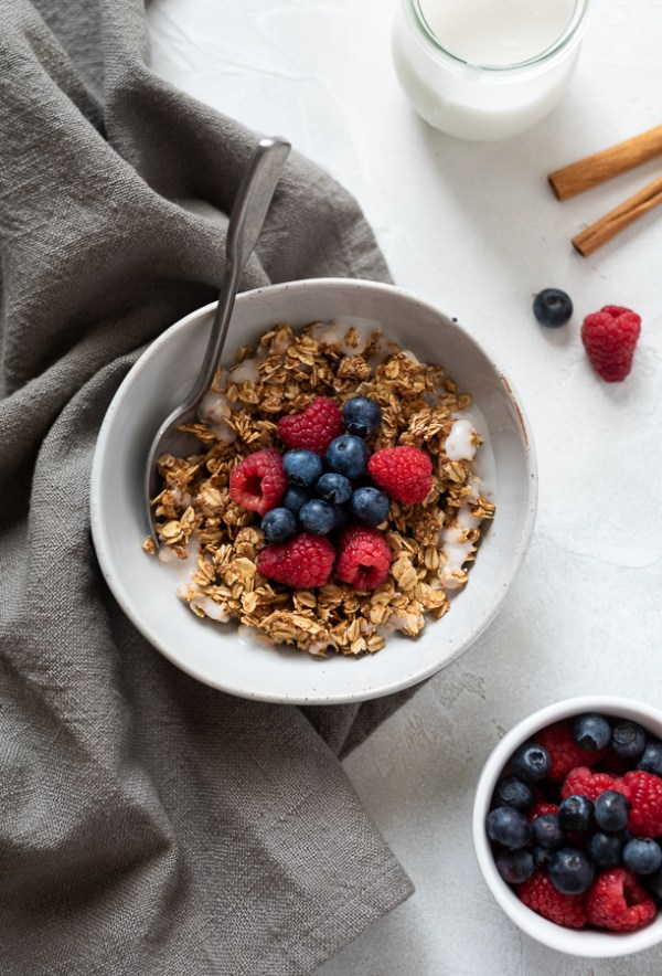 overhead shot of almond butter granola in bowl topped with berries